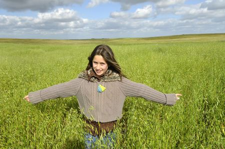 Beautiful young girl outdoors in a green field photo