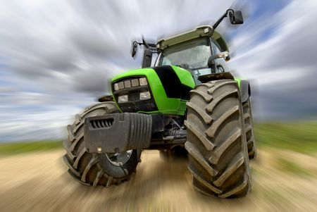 Green tractor in the field with a cloudy sky Stock Photo - 5181053