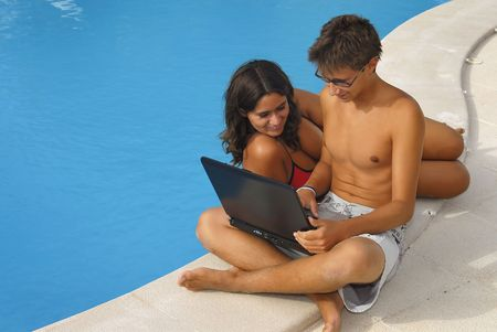 Young couple ith laptop by the pool photo
