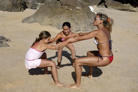 Fitness teacher with children in the beach doing some exercises photo