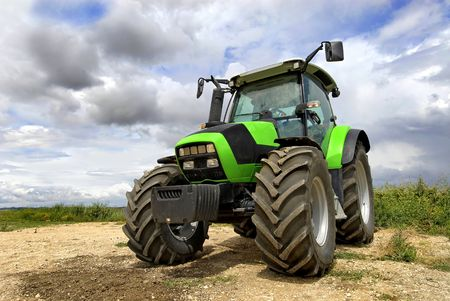 Green tractor in the field with a cloudy sky Stock Photo