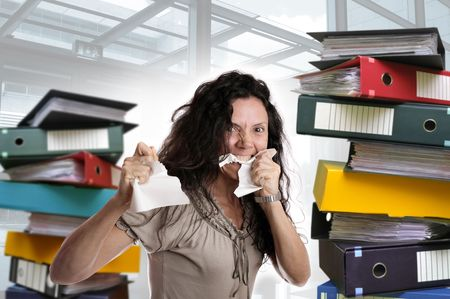 messy office: Insane woman with stacks of files around isolated in white Stock Photo