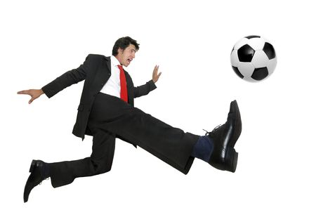 Businessman in a acrobatic pose kicking a soccer ball  isolated in white