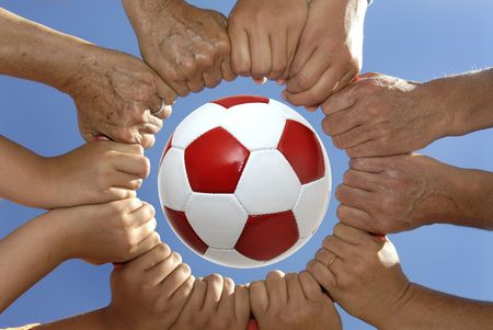 fairplay: Several hands holding together in a circle around a soccer ball