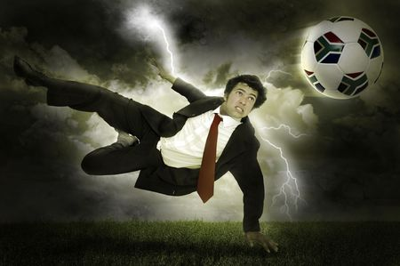Businessman in a acrobatic pose kicking a soccer ball in a stormy field with lightning photo