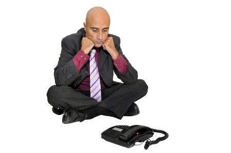 businessman waiting call: Businessman seated on the floor looking at a telephone waiting for a call, isolated in white