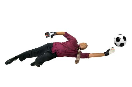 Businessman goalkeeper with gloves  in a acrobatic pose with a soccer ball isolated in white photo