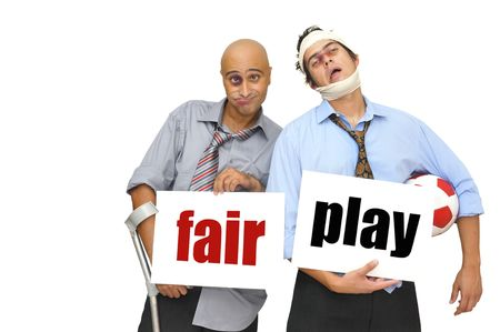 Two badly injured businessmen after a soccer match with cards saying Fair play, isolated in white photo