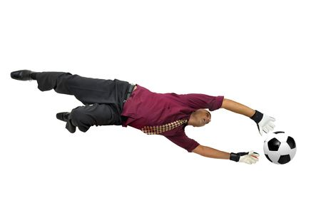 goal keeper: Businessman goalkeeper with gloves  in a acrobatic pose with a soccer ball isolated in white