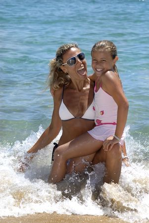child girl nude: Young girl and woman having fun in the beach Stock Photo