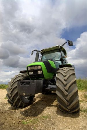 Green tractor in the field with a cloudy sky photo