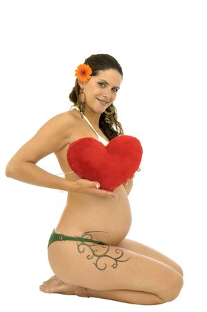 Pregnant woman with tattoo and red heart isolated in white photo