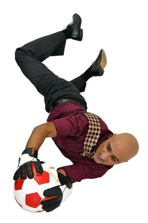 Businessman goalkeeper with gloves and ball in a acrobatic save isolated in white photo