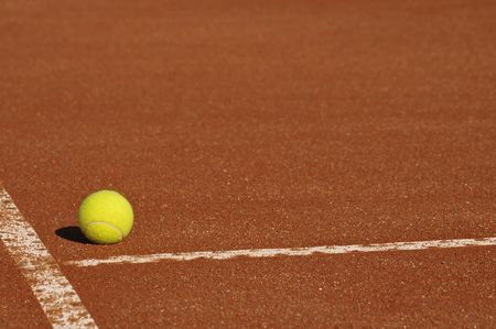 tennis court: Detail of a clay court with tennis ball