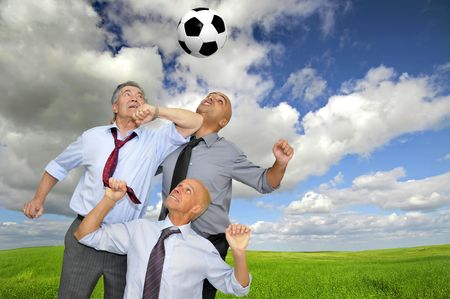 Businessmen playing  soccer outdoors Stock Photo