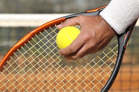 Players hand with tennis ball preparing to serve photo