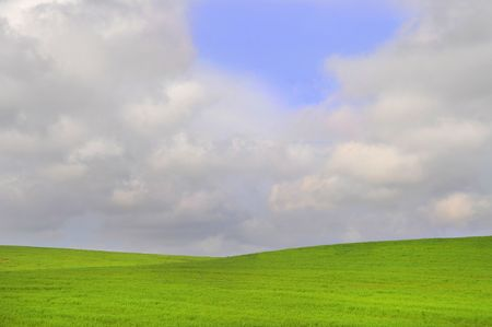 Beautiful green field background with a moody sky photo