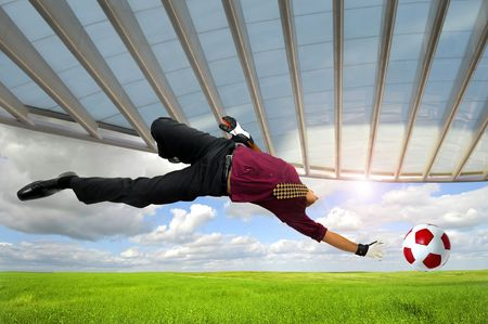 business game: Businessman playing soccer outdoors in a green field Stock Photo