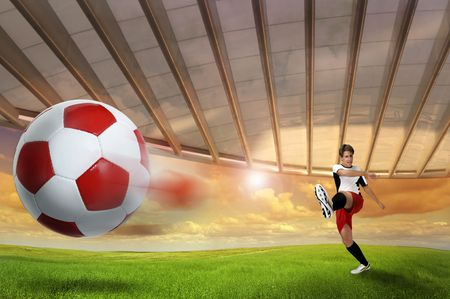 Soccer player kicking a ball outdoors photo