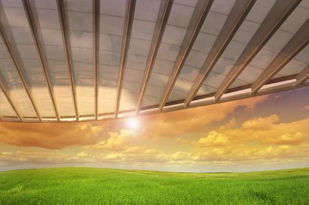 Beautiful wallpaper image of a grass field with  cloudy sky and a moderm roof structure photo