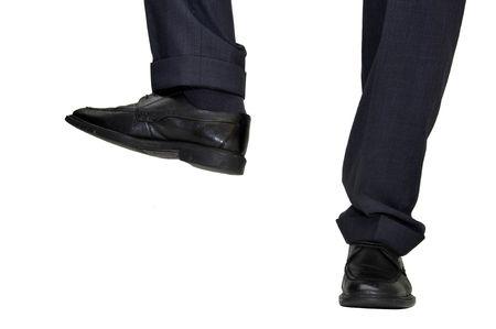 Businessman feet preparing to crush something isolated in white photo