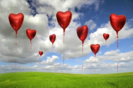 Beautiful image of red heart balloons in a grass field with blue cloudy sky