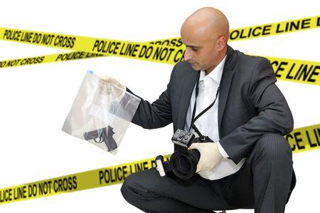 crime solving: Police CSI investigator with a camera holding a bag with a gun