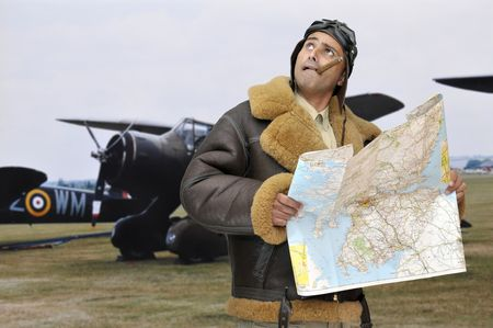 WWII fighter pilot with map looking to the sky photo