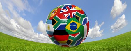 Soccer ball with flags in a green field with blue cloudy sky photo