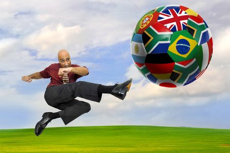 Businessman playing soccer outdoors in a green field photo
