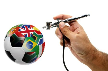 airbrush: Hand with airbrush painting world cup country flags in a soccer ball isolated in white Stock Photo