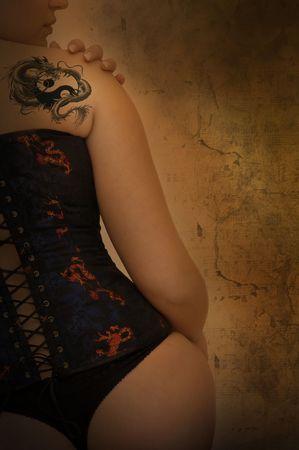 corsetto: Sexy woman con tatuaggio corsetto e Drago in uno sfondo grunge