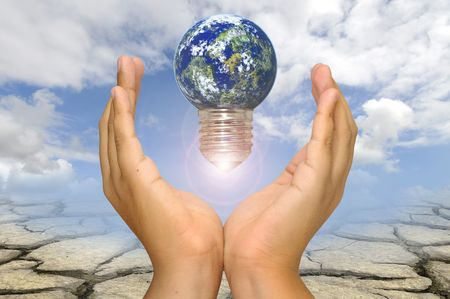 Hands with earth lightbulb  over a dry soil and sky background photo