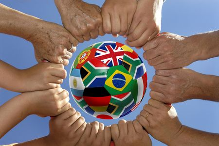 fairplay: Several hands holding together in a circle around a soccer ball with flags
