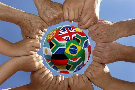 manos unidas: Varias manos celebrar juntos en un c�rculo alrededor de un bal�n de f�tbol con banderas