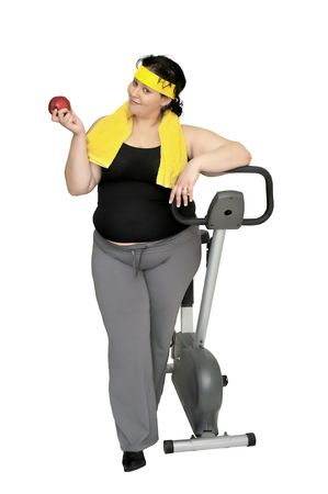 Large girl with a fitness bicycle and an apple  photo