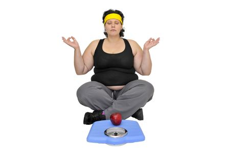 Large girl sitting near a scale with an apple doing yoga exercises photo