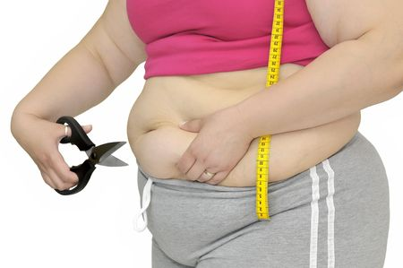 gluttonous: Body part of a fat woman with measuring tape and scissors Stock Photo