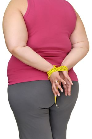 Body part of a fat woman with hands tied up with measuring tape photo