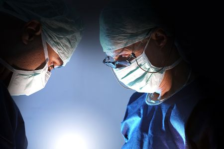 medical procedure: Doctors team in surgery in a dark background Stock Photo