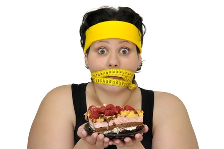 Large girl gaged with measuring tape holding a cake isolated in white photo