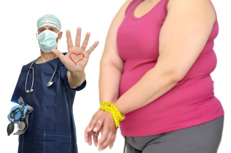 gluttonous: Out of focus fat woman with hands tied up with measuring tape and doctor Stock Photo