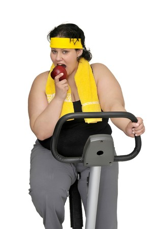 Large girl with fitness bicycle holding an apple isolated in white photo
