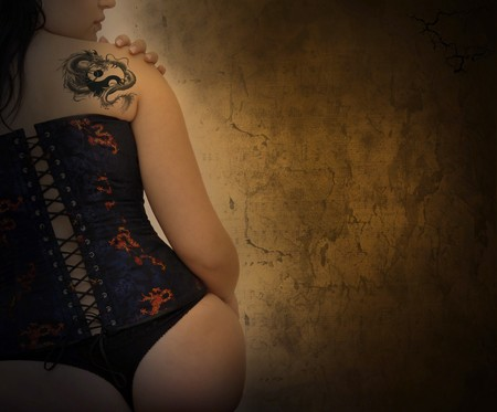 dragon tattoo: Sexy woman with corset and dragon tattoo in a grunge background