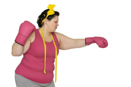 Large girlwith boxing gloves beating  a scale isolated in white photo