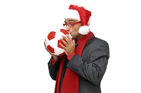Businessman kissing a soccer ball in Christmas time photo
