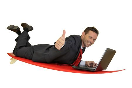 Young businessman laying in a surf board with laptop Stock Photo - 7641221