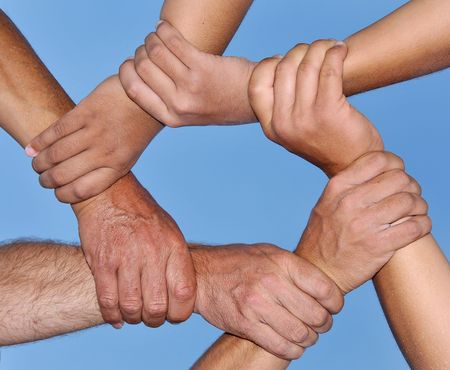 strong partnership: Human hands in a strong link against a deep blue sky