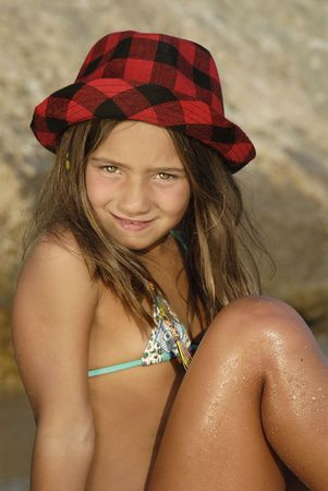 Beautiful young girl posing with hat in the beach photo