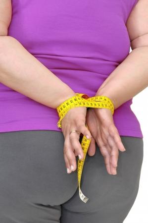 mujer gorda: Parte del cuerpo de una mujer grasa con manos atado con cinta de medici�n